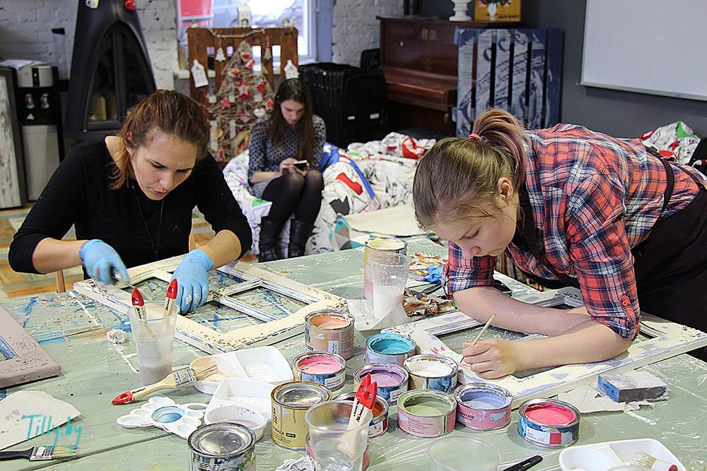 Девушки наносят собственные рисунки на декорированные окошки